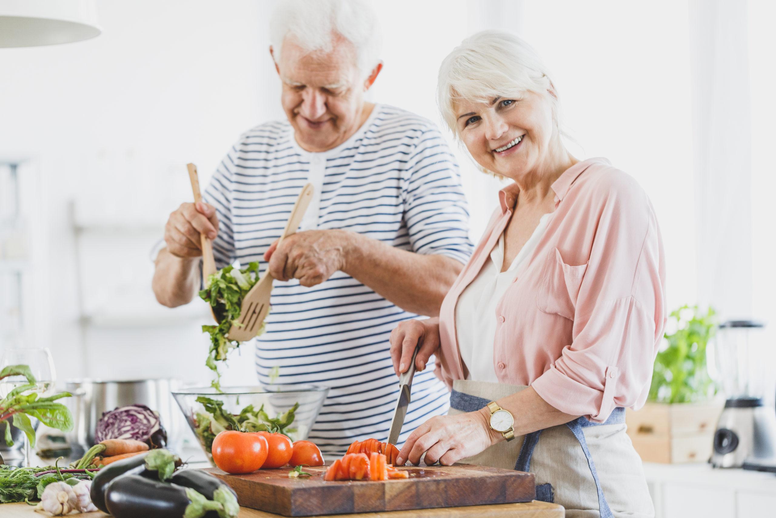 coppia che cucina e sorride